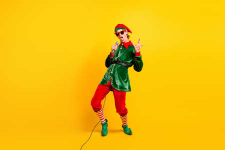 Full length body size view of his he nice attractive cool naughty funny guy elf singing hit having fun showing horn symbol isolated over bright vivid shine vibrant yellow color background Stock Photo