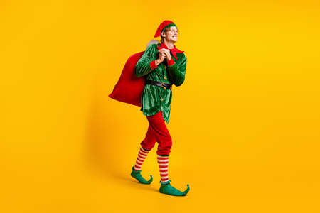 Full length body size view of his he nice attractive cheerful cheery funny guy elf walking carrying sack wintertime day delivery isolated over bright vivid shine vibrant yellow color background
