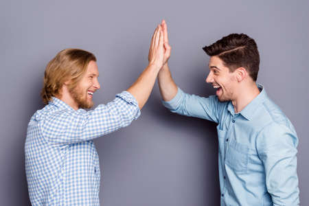 Profile side view portrait of two nice attractive glad cheerful cheery guys best buddy fellow clapping palms deal done success team isolated over gray purple pastel color background