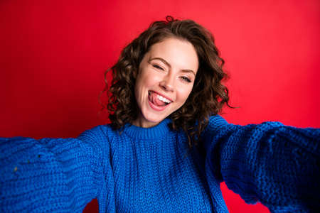 Closeup photo of cute pretty lady curly hairdo take selfie having fun tongue-out blink eye lick teeth carefree wear blue knitted sweater pullover jumper isolated red color background Stock fotó