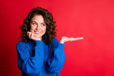 Photo of cute lady wavy hairstyle hand hold look empty space arm cheekbone cozy interested toothy smile wear blue knitted pullover isolated red color background