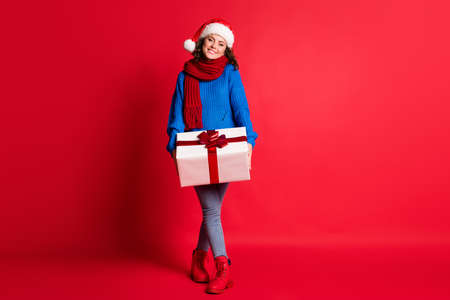 Full length body size view of her she attractive pretty lovely cheerful cheery girl wearing festal look carrying large giftbox st Nicholas isolated bright vivid shine vibrant red color background