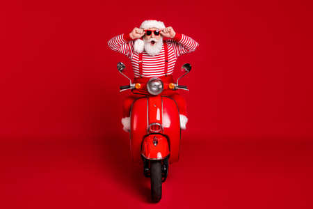Portrait of his he handsome amazed wondered impressed stunned funny cheerful bearded Santa riding moped having fun journey isolated bright vivid shine vibrant red color background