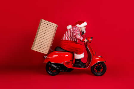 Full length profile photo of retired grandpa scooter ride highway instant deliver pizza wear santa x-mas costume suspenders sunglass boots striped shirt cap isolated red color background