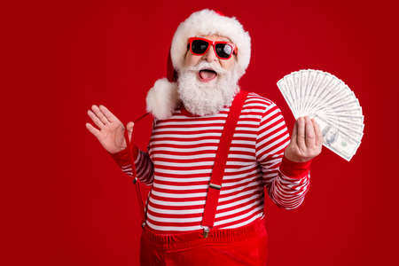 Photo of pensioner old man grey beard hold money cash fan play strap have fun millionaire wear santa x-mas costume suspenders spectacles striped shirt cap isolated red color background
