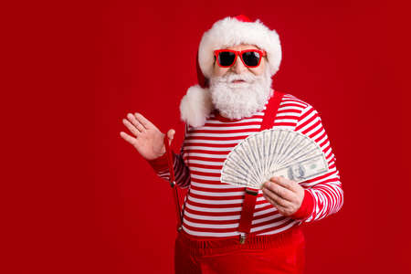 Photo of retired grandpa grey beard hold money cash fan play strap empty space prepare trip tropics wear santa x-mas costume suspenders spectacles striped shirt cap isolated red color background