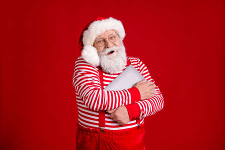 Portrait of nice handsome cheerful cheery bearded Santa father holding in hands hugging laptop North Pole December wintertime isolated bright vivid shine vibrant red color background