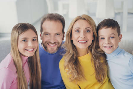 Photo of idyllic family mom dad and two children boy girl look in camera toothy smile sit couch in house indoors