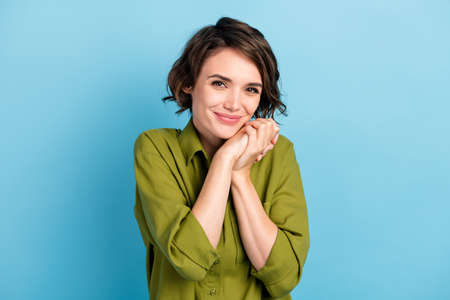 Photo portrait of sweet lovely romantic young girl putting hands together with short hairstyle wearing green shirt smiling isolated on blue color background