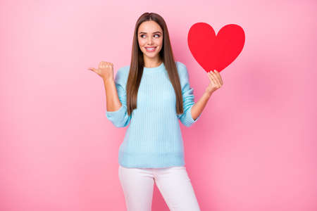 Photo of attractive lady hold big paper red heart direct thumb finger empty space creative postcards shop wear knitted blue sweater white pants isolated pastel pink color background 스톡 콘텐츠