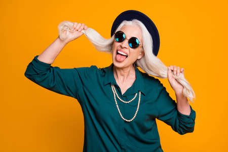 Photo of pretty funky white hair grandma lady cool look hold long curls hands stick tongue out mouth wear green shirt sun specs necklace retro hat isolated bright yellow color background