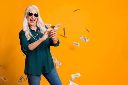 Photo of funky granny lady pack usa bucks hands money fall sky wealthy person spend money luxury wear green shirt sun specs necklace jeans isolated bright yellow color background