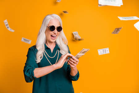 Photo of funky crazy grandma lady pack usa bucks hands money fall sky wealthy person spend money luxury wear green shirt sun specs necklace isolated bright yellow color background Фото со стока