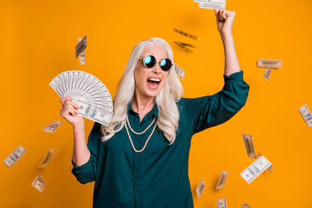 Photo of funky grandma lady hold fan usa bucks money fall from sky wealthy rich person freelance job income wear green shirt sun specs necklace isolated bright yellow color background Фото со стока