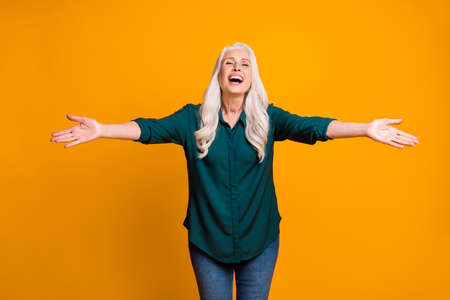 Hug me Photo of cheerful white haired grandma lady spread open arms meet grandchildren airport bus train station wear green shirt jeans isolated vivid yellow color background 版權商用圖片