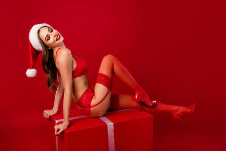 Full size profile portrait of snow girl sit on x-mas package wear provocative boudoir isolated on red color background