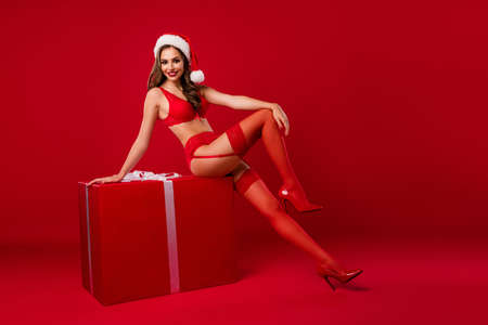 Full size portrait of beautiful lady sit on x-mas package wear stilettos smiling teasing isolated on red color background