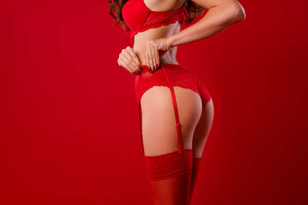 Cropped photo portrait of girl pulling garter belt up isolated on vivid red colored background