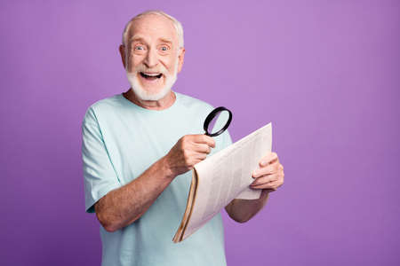 Portrait of funny optimistic grey beard hair pensioner holding magnifier newspaper isolated over violate background