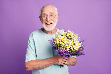 Portrait of smiling positive old man holding bunch flowers wear blue t-shirt isolated over purple color background