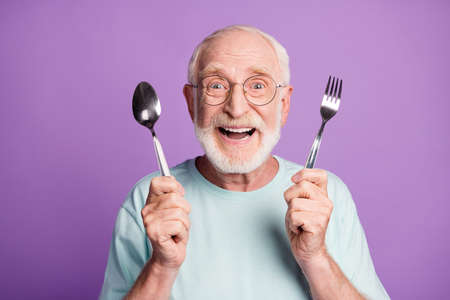 Photo of positive smiling grandfather hold cutlery wear light blue t-shirt isolated over violet color background