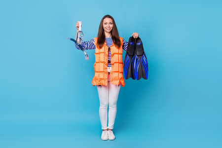 Full length body size view of her she attractive cheerful cheery girl wearing float orange vest holding in hands scuba equipment accessory isolated bright vivid shine vibrant blue color background