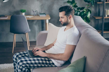 Profile side photo of smart cool boss man sit couch in sleepwear nightwear outfit work remote laptop have online communication with agent investor in house indoors Imagens