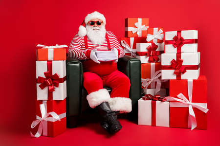 Photo of santa claus sit armchair hold kids mail wear x-mas suspenders headwear glasses isolated decorated red color background