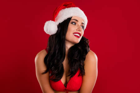 Photo of pretty brown haired woman look empty space wear bra imagine present xmas isolated on red color background