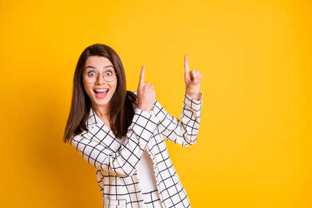 Photo of impressed student girl wear plaid jacket pointing empty space two fingers isolated yellow color background