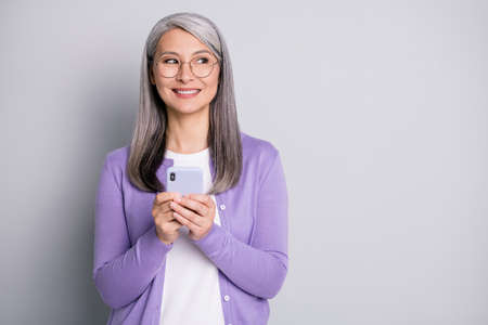 Portrait photo of positive granny using cellphone texting browsing internet typing message wearing eyeglasses smiling isolated on grey color background 免版税图像