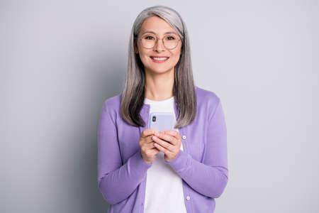 Portrait photo of positive old woman using cellphone texting browsing internet communicating wearing eyeglasses smiling isolated on grey color background 免版税图像
