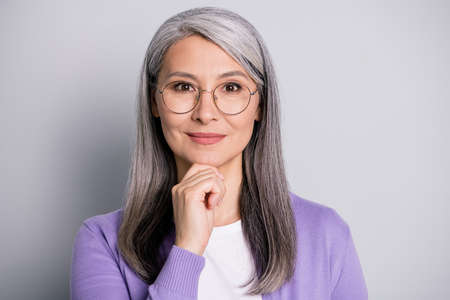 Portrait photo of smart clever woman wearing eyeglasses smiling pleasantly satisfied touching face isolated on grey color background
