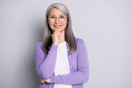 Portrait photo of smart elder intelligent female professor in the university wearing eyeglasses smiling touching face isolated on grey color background Foto de archivo