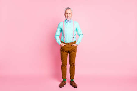 Full length body size portrait of man wearing bowtie suspenders brown pants keeping hands in pockets isolated on pink color background