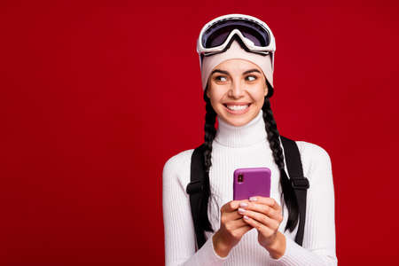 Photo of young attractive lovely smiling cheerful positive girl using smartphone look copyspace isolated on red color background