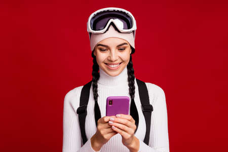 Portrait of young beautiful smiling cheerful positive good mood girl using smartphone isolated on red color background