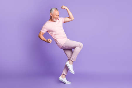 Full length profile photo of retired man raise fist knee palms wear pink t-shirt trousers sneakers isolated violet color background