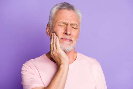 Close-up portrait of his he nice attractive sick grey-haired man touching cheek jaw feeling tooth pain caries isolated over bright vivid shine vibrant lilac purple violet color background
