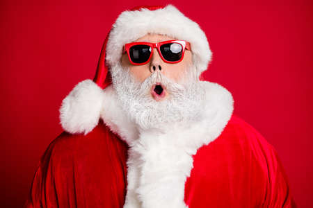 Close-up portrait of his he nice handsome amazed bearded Santa father St Nicholas pout lips cool celebratory event season sale isolated bright vivid shine vibrant red color background