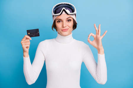 Photo of brunette girl hold credit card show ok sign wear hat shopper winter season isolated on blue color background