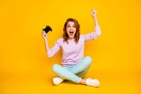 I win Unbelievable Full size photo delighted competitive girl sit legs crossed play video games celebrate victory raise fists scream wear pink turquoise pants jumper isolated shine color background