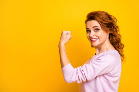 Profile photo of confident cheerful wavy lady raise fist up showing strong biceps muscle toothy smiling wear casual pink pullover isolated yellow color background
