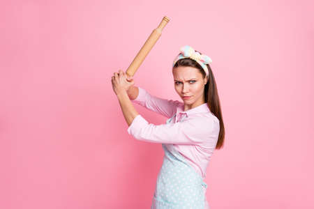 Portrait of her she nice attractive dangerous mad serious housewife holding in hands rolling pin threatening fighting rights gender equality isolated over pink pastel color background