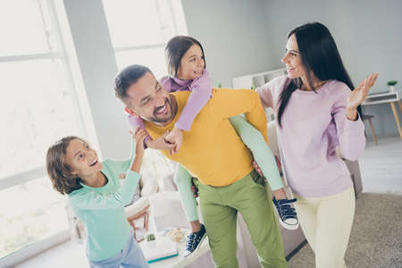 Photo of full family four members talk two small kids daddy hold piggy back daughter wear colorful sweater pants in living room indoors