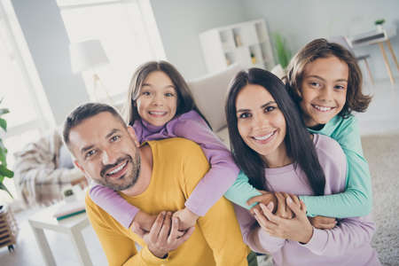 Photo of full family four people parents hold piggy back kids wear colorful sweater in living room indoors