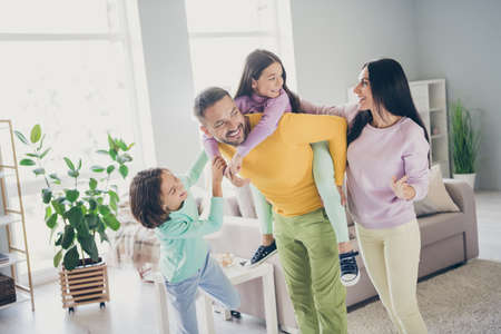 Photo of full family four members daddy hold piggy back daughter enjoy weekend wear colorful jumper trousers in living room indoors