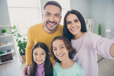 Photo of full family four people mommy take selfie hug beaming smile wear colorful sweater in living room indoors