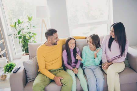 Photo of full family four people sit couch son hands daughter smile wear colorful pullover in living room indoors