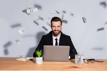 Photo of macho business guy notebook table bucks american falling toothy smiling rich chief success startup income wear blazer shirt tie suit sit chair isolated grey background Фото со стока